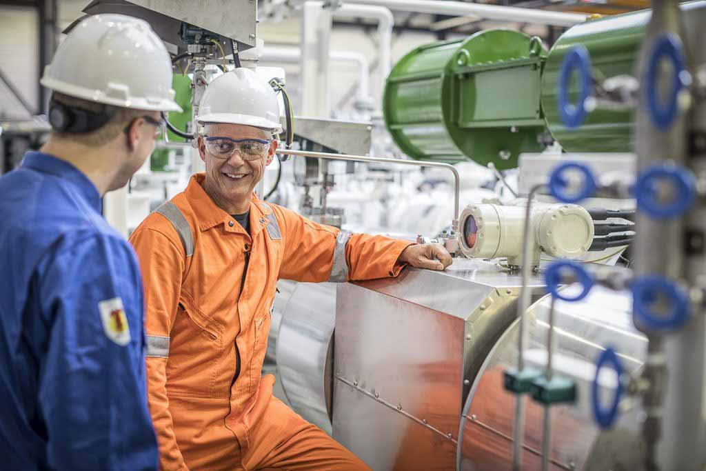 Two people smiling while on a gas flow meter service.